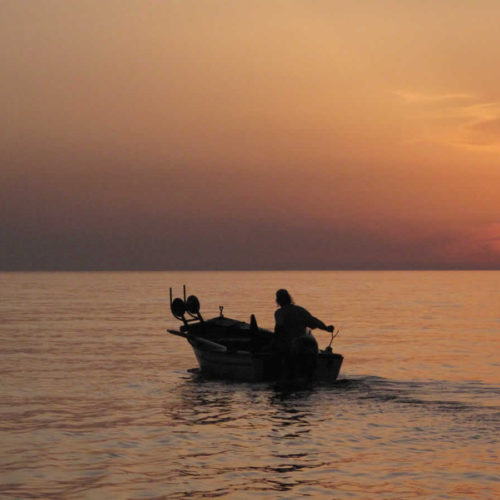 fisherman in his boat during sunset in Panormos bay, Tinos